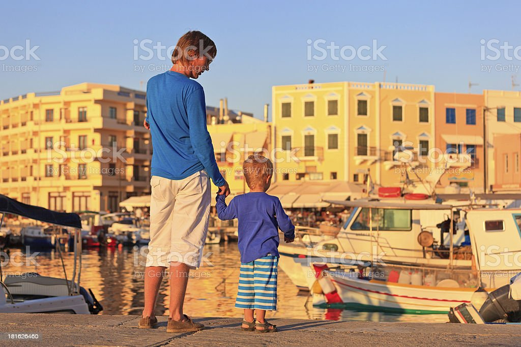 father and son on the quay in Crete, Greece royalty-free stock photo