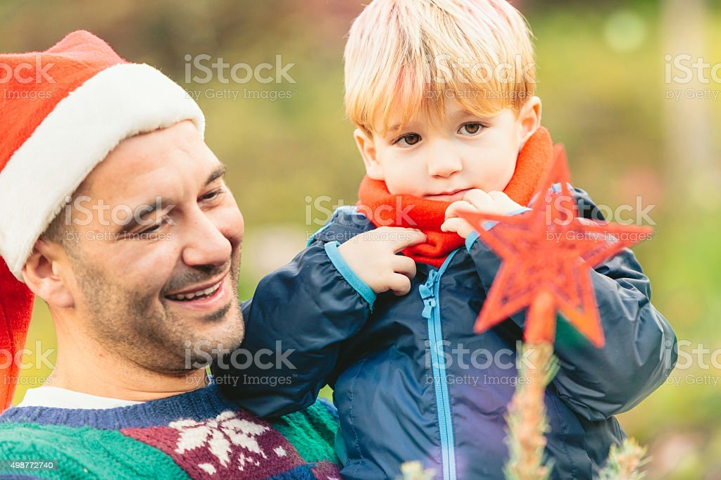 father and son outdoor decorating christmas tree stock photo