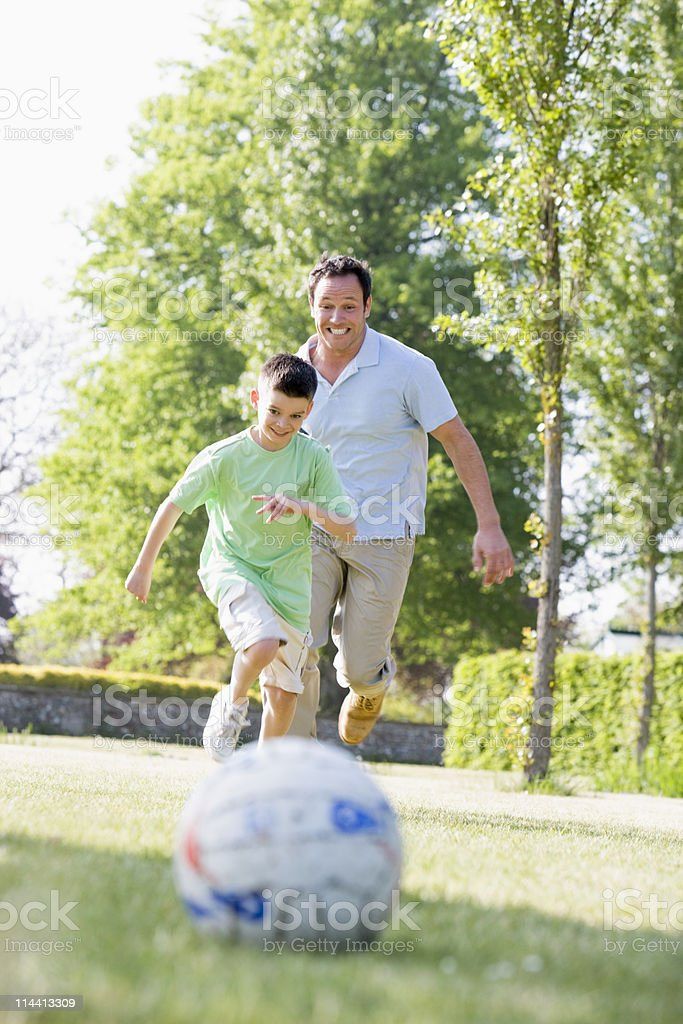 Father and son outdoors playing soccer royalty-free stock photo