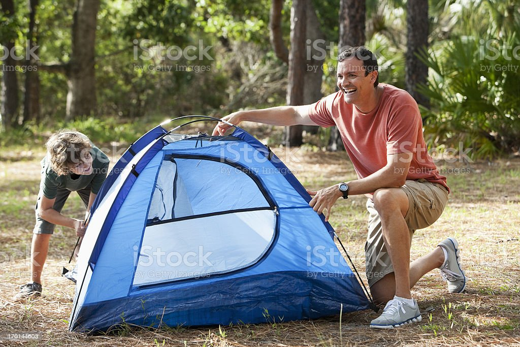 Father and son pitching a tent stock photo
