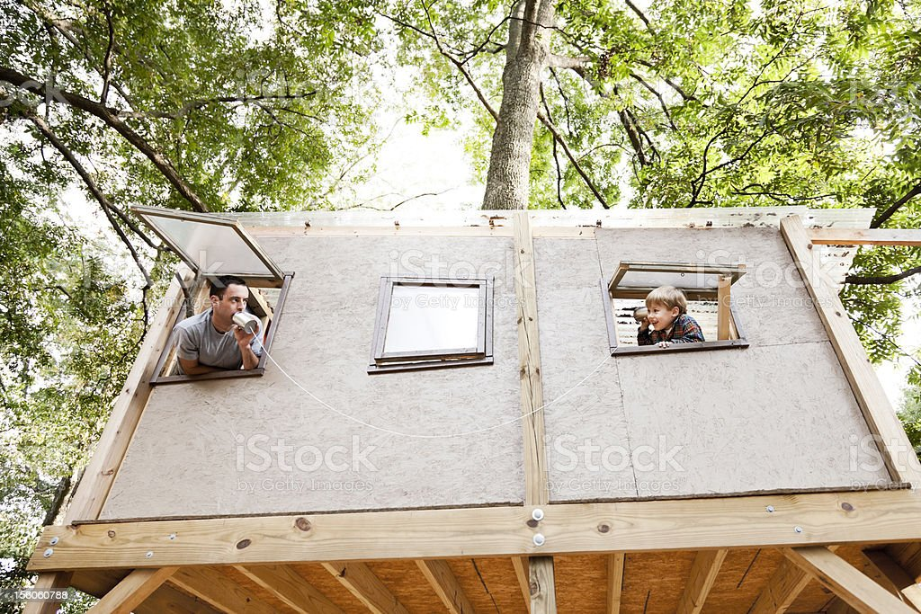 Father and Son Play Telephone in a Tree House stock photo