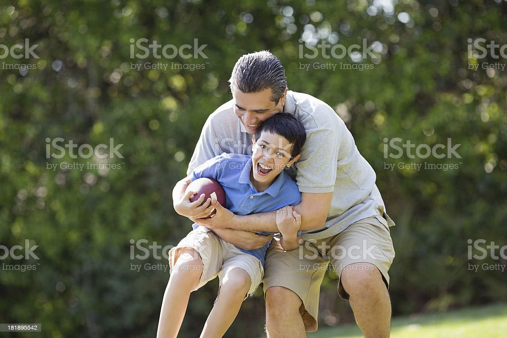 Father And Son Playing American Football At Park royalty-free stock photo