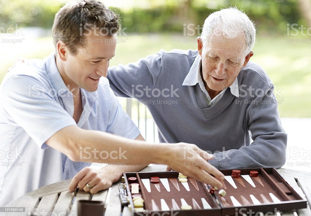 Father and son playing backgammon in a park stock photo