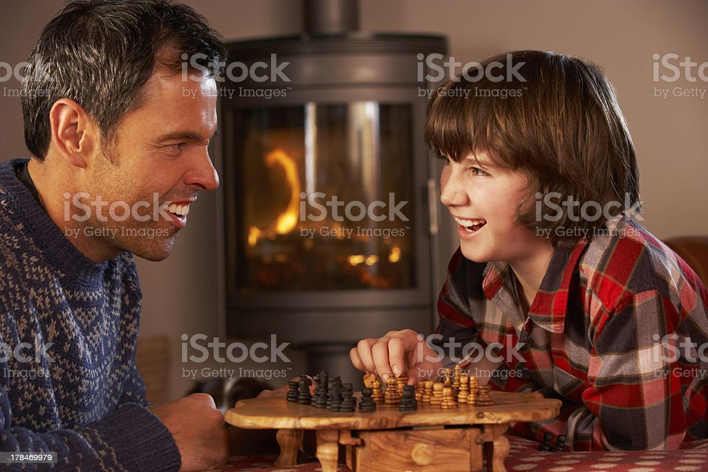 Father And Son Playing Chess By Cosy Log Fire stock photo