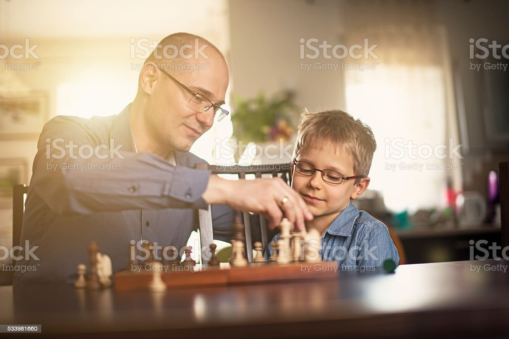 Father and son playing chess together stock photo