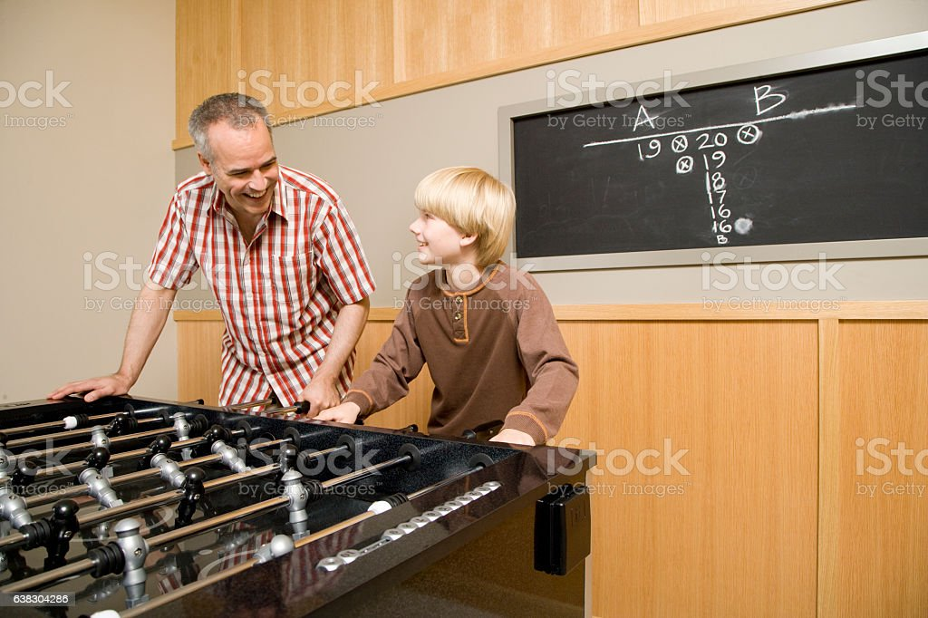 Father and son playing foosball together at home stock photo
