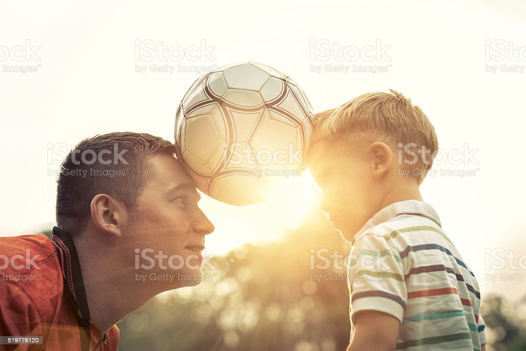 Father and son playing football in park at sunny day stock photo
