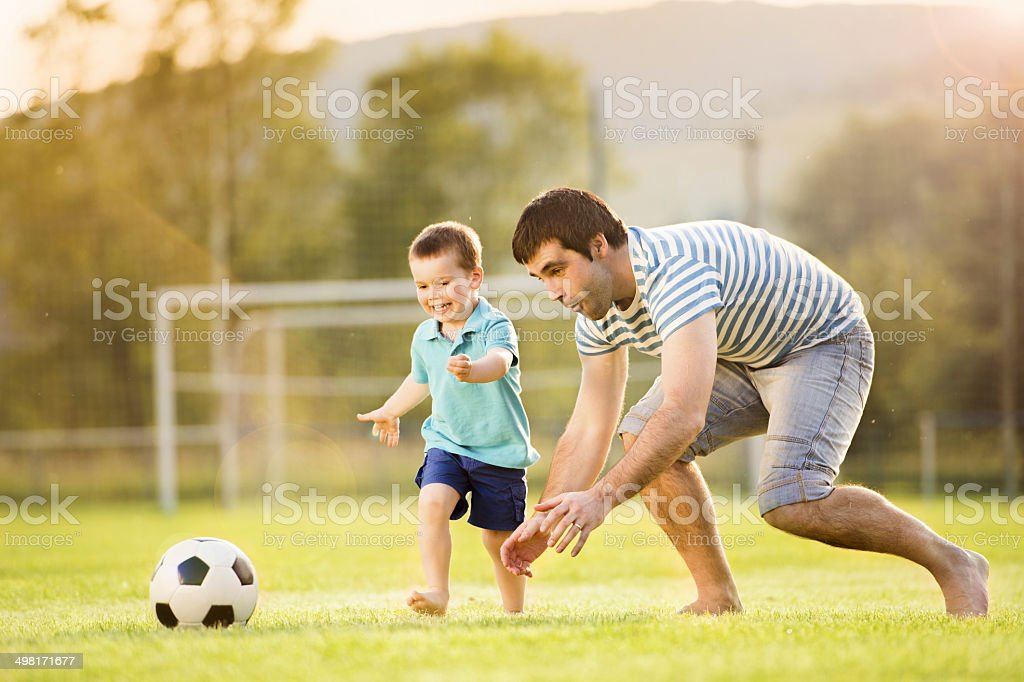 Father and son playing football stock photo