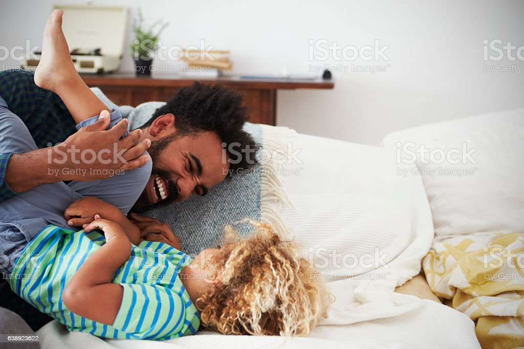 Father And Son Playing Game On Sofa Together stock photo