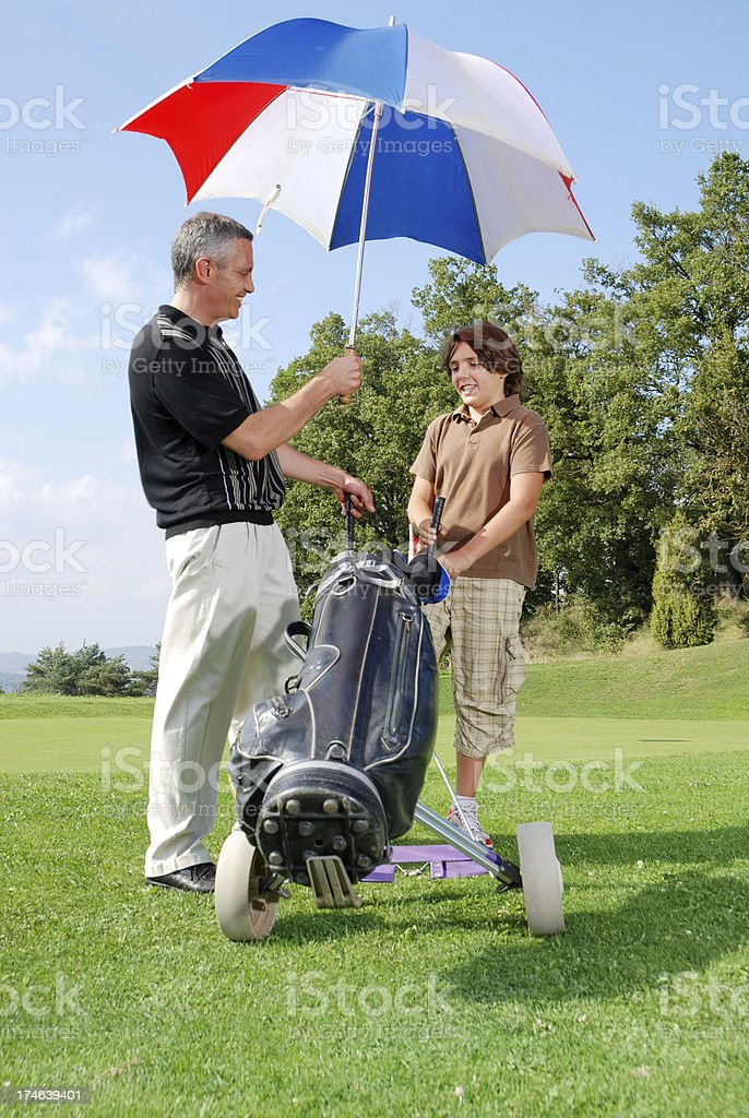 Father and son playing golf royalty-free stock photo