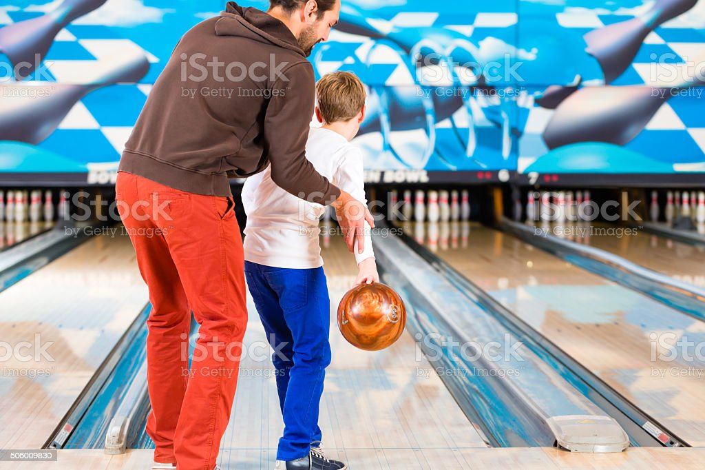 Father and son playing in bowling center stock photo
