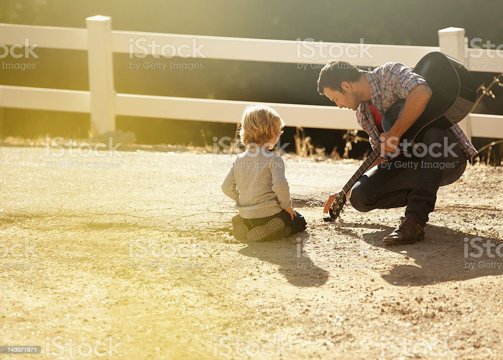 Father and son playing in dirt road royalty-free stock photo