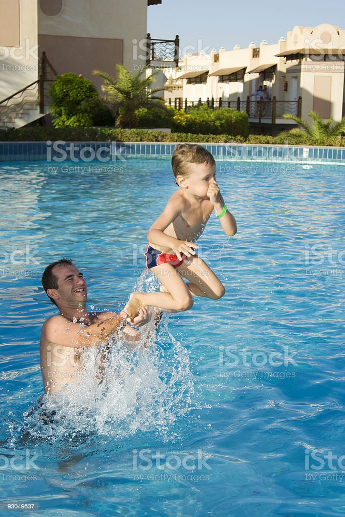 Father and son playing in pool royalty-free stock photo