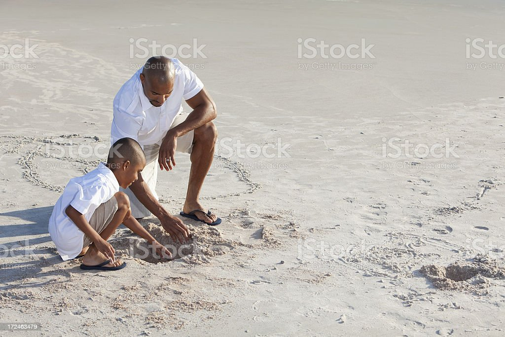 Father and son playing in sand at beach stock photo