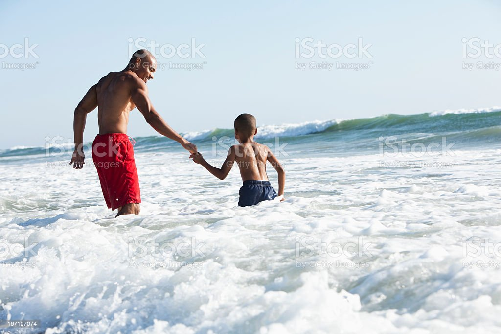Father and son playing in surf royalty-free stock photo