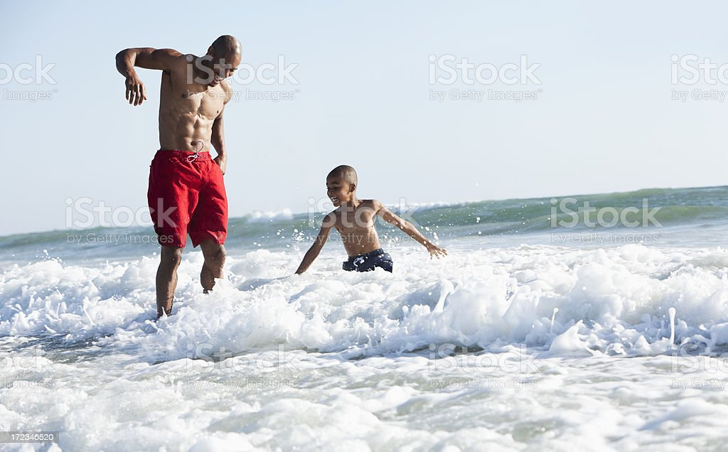 Father and son playing in surf stock photo