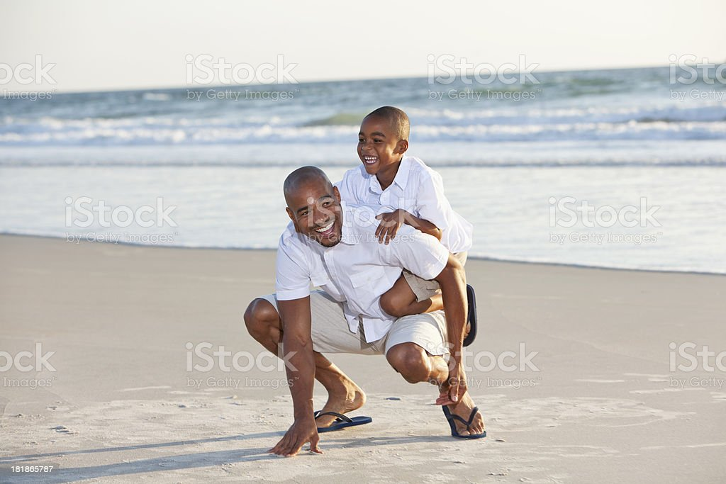 Father and son playing on beach stock photo