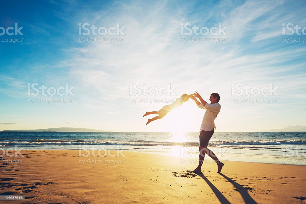 Father and Son Playing on the Beach at Sunset stock photo