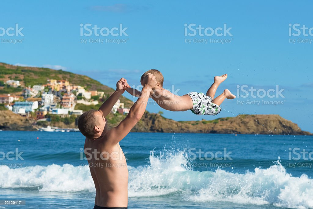 Father and son playing on the beach. stock photo