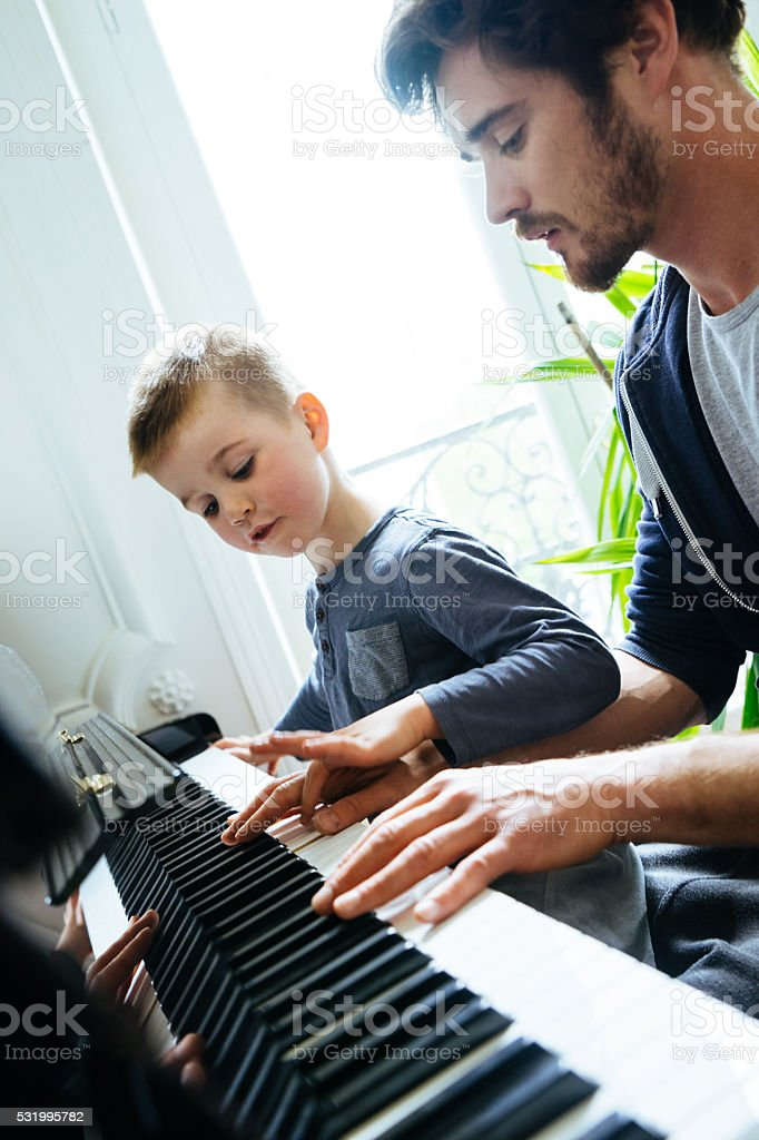 Father And Son Playing Piano Together At Home stock photo