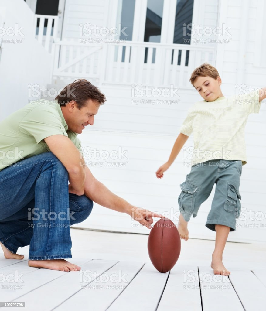 Father and son playing rugby royalty-free stock photo