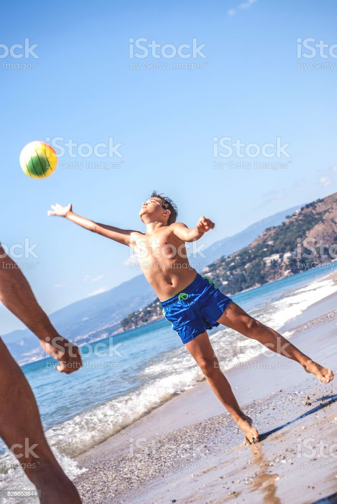 Father And Son Playing Volleyball On The Beach stock photo