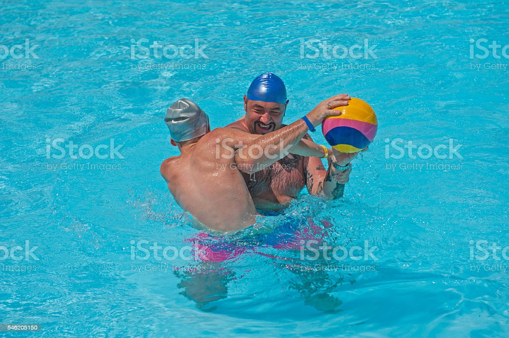 Father and son playing water in tropical resort pool stock photo