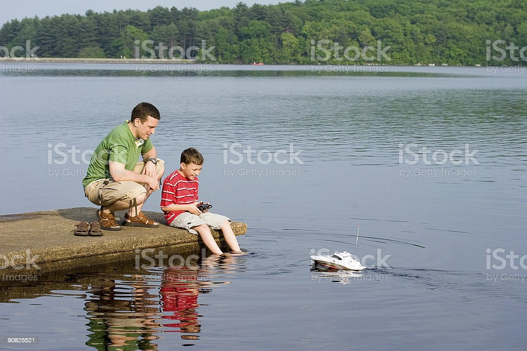 Father and son playing with a toy boat stock photo