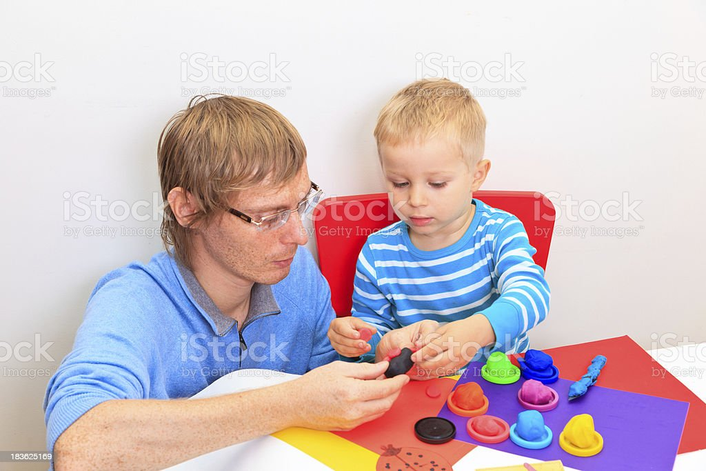 father and son playing with plasticine royalty-free stock photo