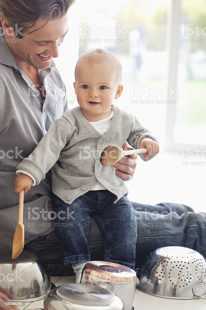 Father and son playing with pots and wooden spoons royalty-free stock photo