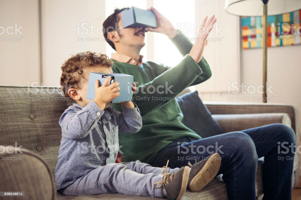 Father and son playing with virtual reality headsets. stock photo