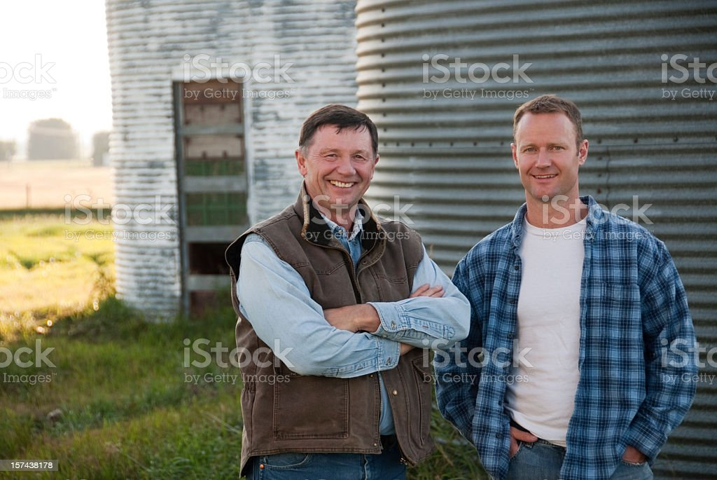 A father and son posing for a photo at a family farm stock photo