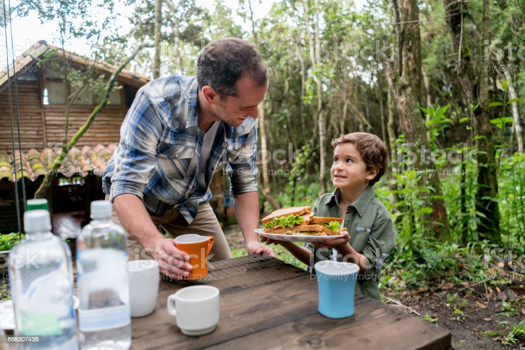 Father and son preparing food outdoors and looking happy stock photo