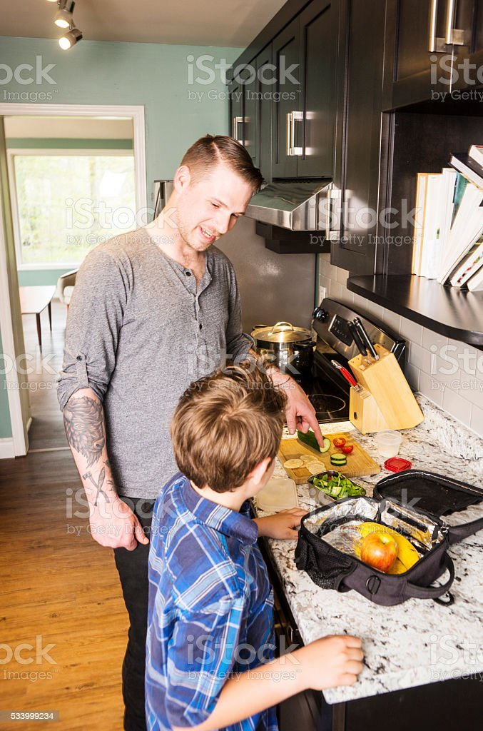 Father and son preparing school lunch stock photo