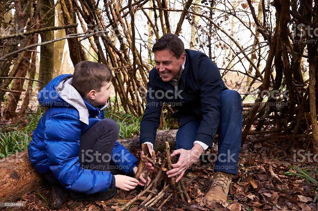 Father and son preparing wood for a campfire, horizontal stock photo