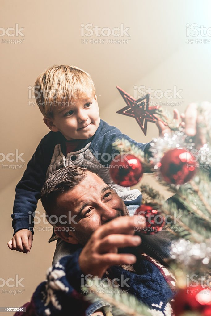 Father and son put tree topper on the Christmas tree stock photo