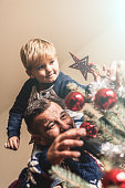 Father and son put tree topper on the Christmas tree