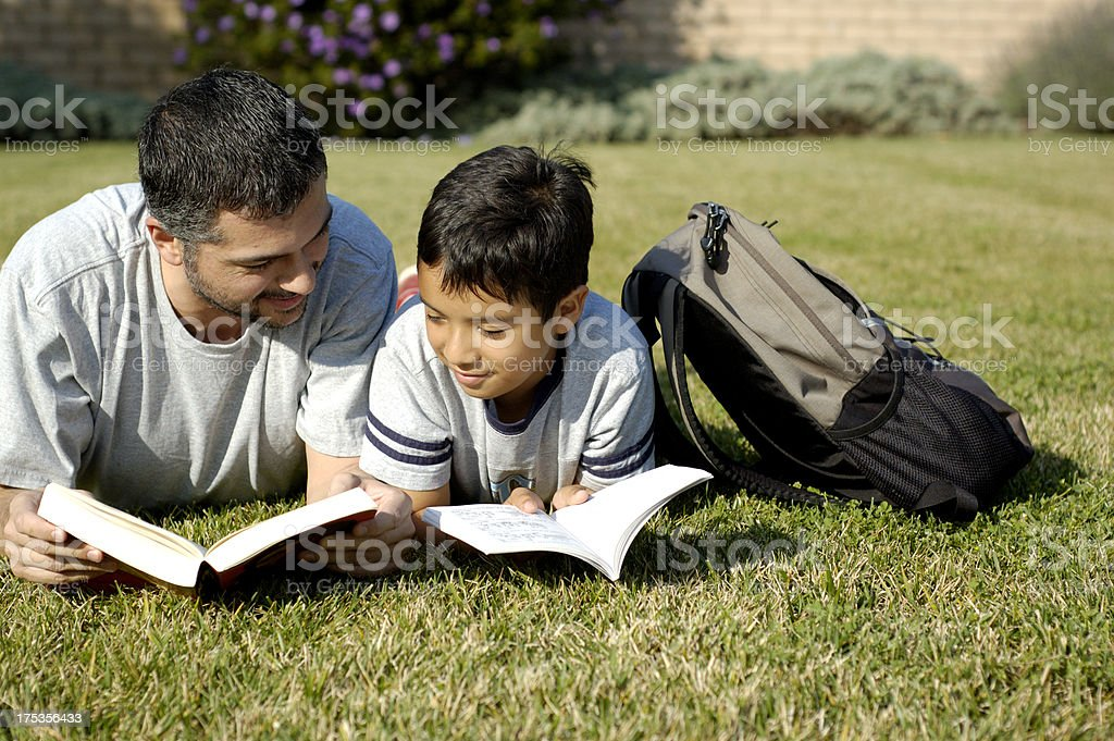 A father and son reading books on a grass lawn stock photo