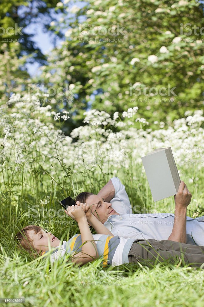 Father and son relaxing in grass royalty-free stock photo