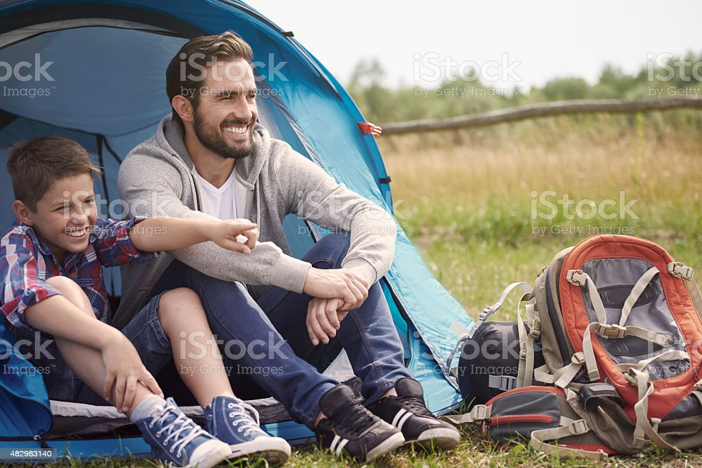 Father and son resting outside the tent stock photo