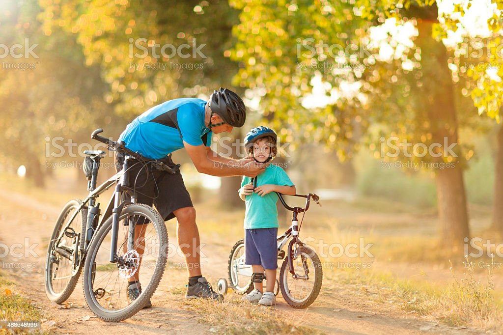 Father and son riding bicycles stock photo
