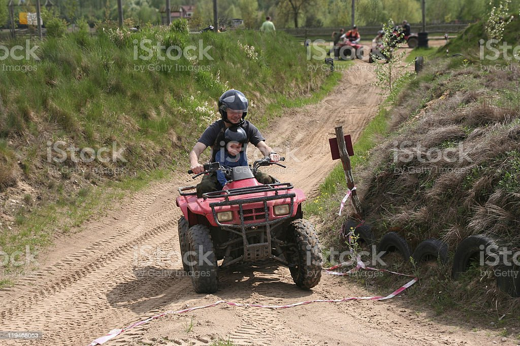 Father and son riding four-wheelers on a muddy trail stock photo