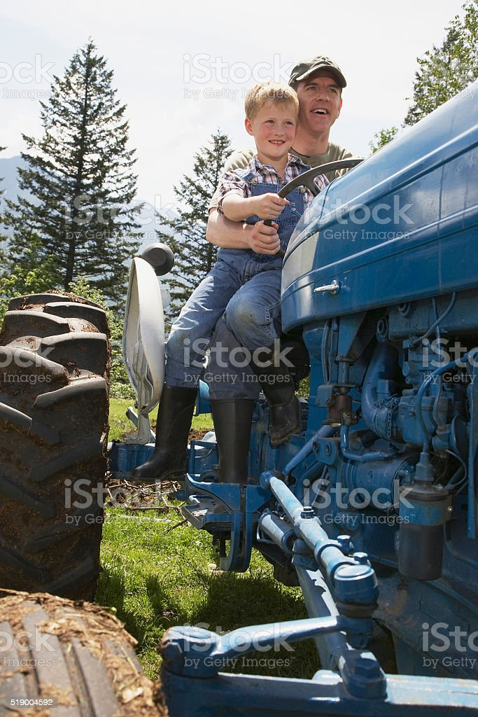 Father and son riding tractor stock photo
