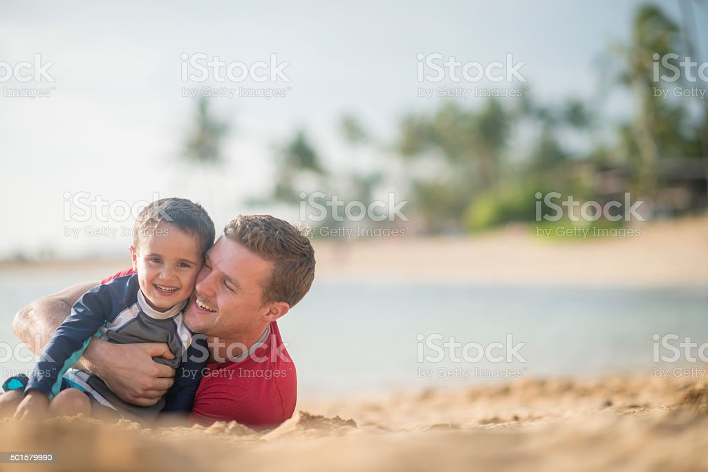 Father and Son Rolling in the Sand stock photo