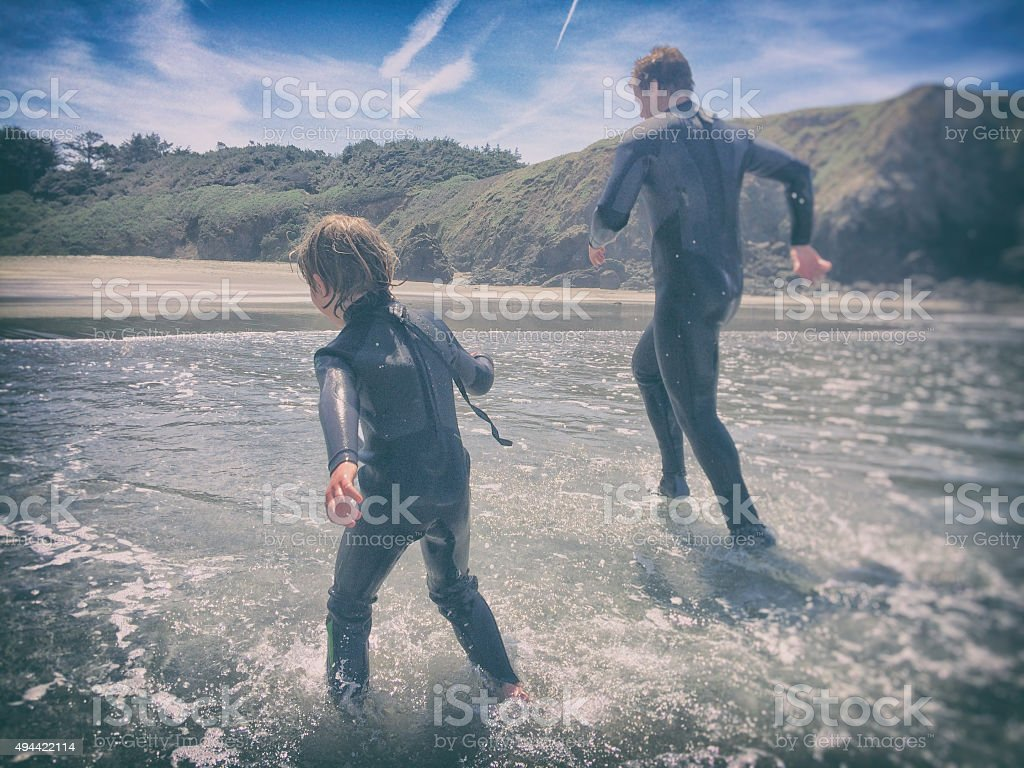 Father and son run in the ocean together stock photo