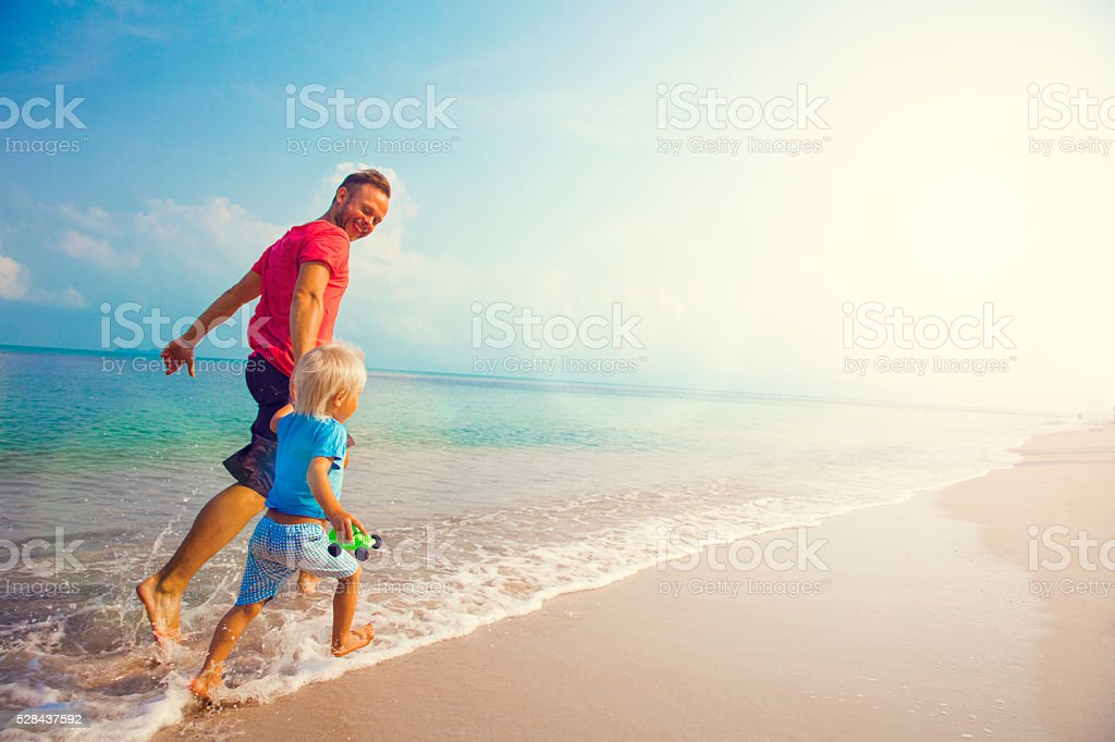 Father And Son Running Along Beach stock photo
