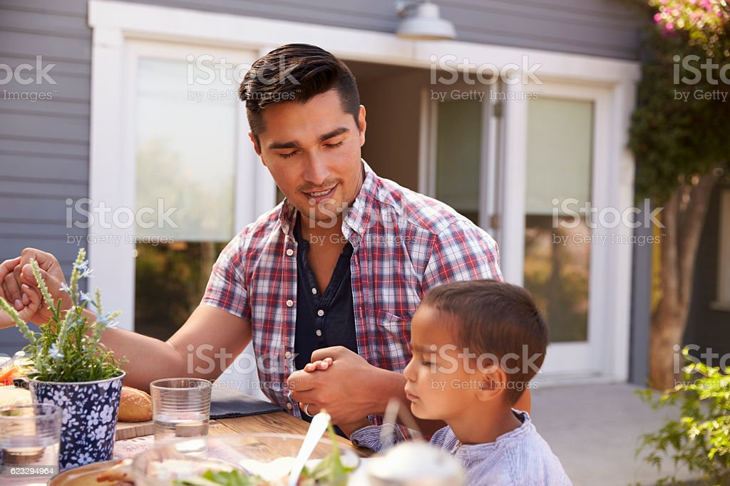 Father And Son Saying Grace Before Outdoor Meal In Garden stock photo