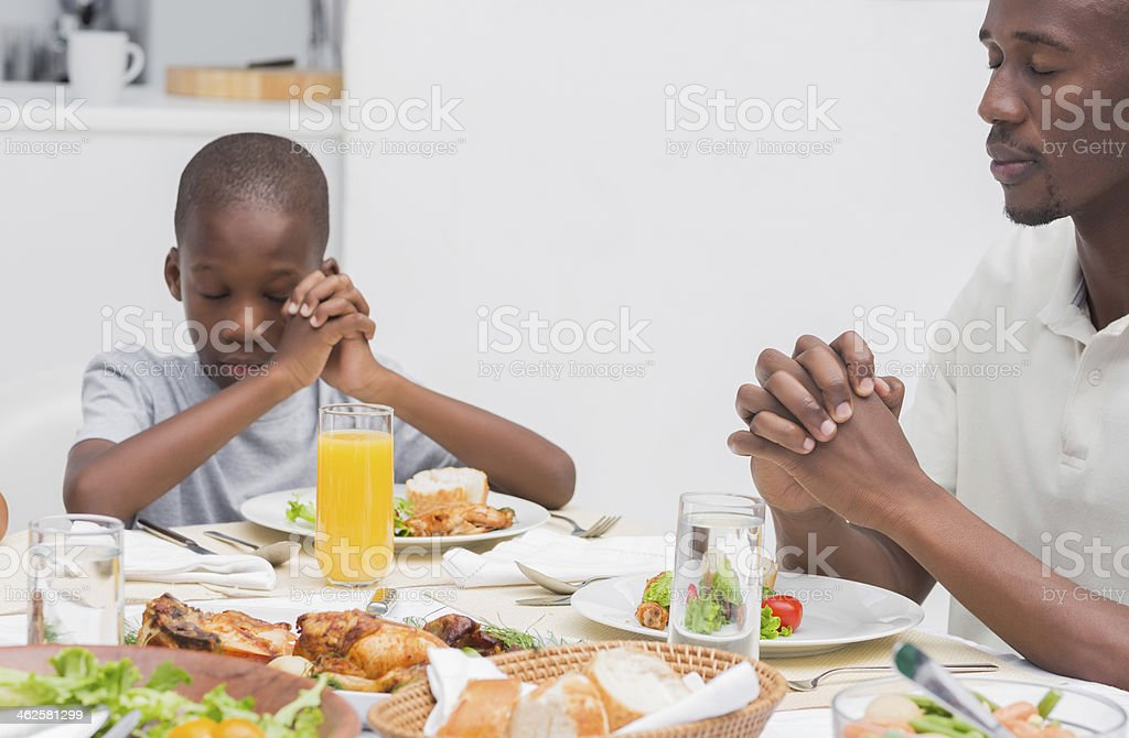 Father and son sayng grace before dinner royalty-free stock photo
