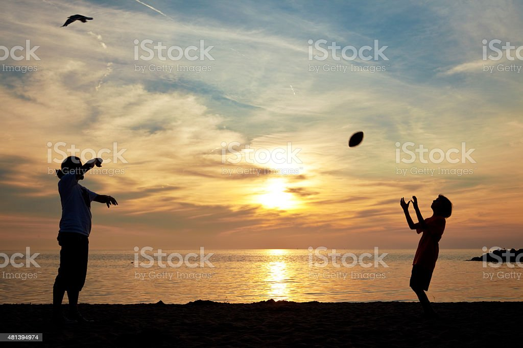 Father And Son Silhouette Playing Football On Beach stock photo