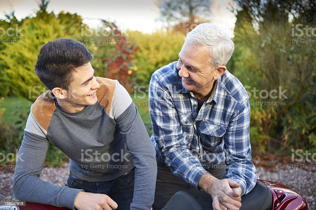 A father and son sitting and looking at each other smiling stock photo
